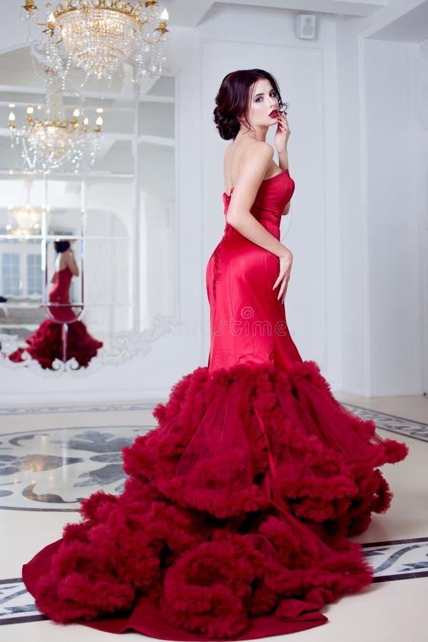 Kvinna för skönhetbrunettmodell i röd klänning för afton Lyxig makeup för härligt mode och frisyr, full längd arkivfoto