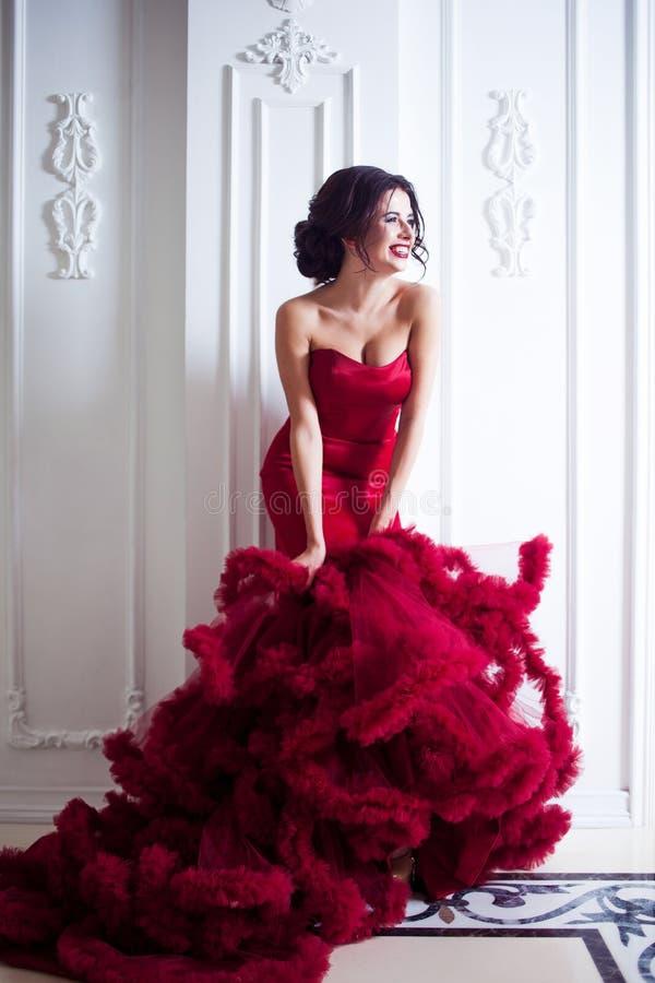 Kvinna för skönhetbrunettmodell i röd klänning för afton Lyxig makeup för härligt mode och frisyr, full längd arkivbild
