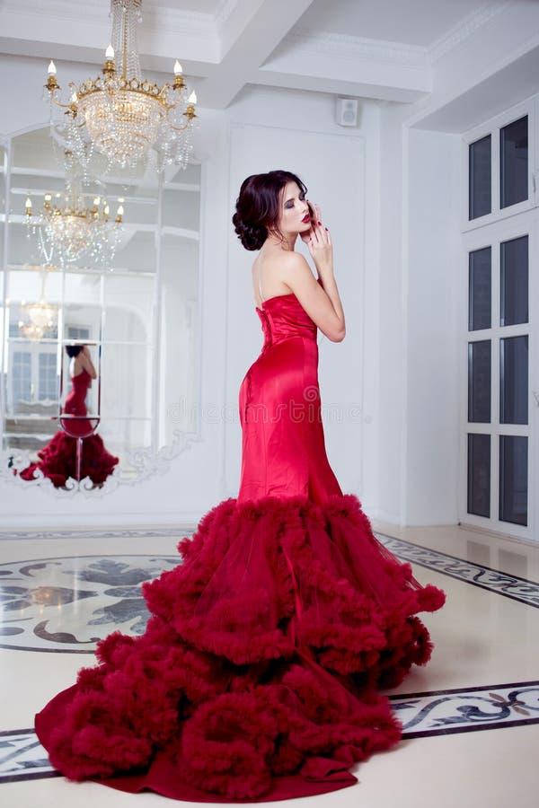 Kvinna för skönhetbrunettmodell i röd klänning för afton Lyxig makeup för härligt mode och frisyr, full längd arkivfoton