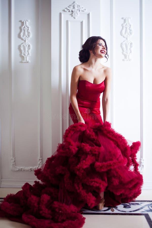 Kvinna för skönhetbrunettmodell i röd klänning för afton Lyxig makeup för härligt mode och frisyr, full längd royaltyfri bild