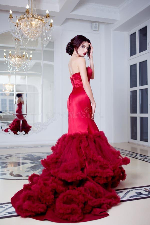 Kvinna för skönhetbrunettmodell i röd klänning för afton Lyxig makeup för härligt mode och frisyr, full längd royaltyfria foton