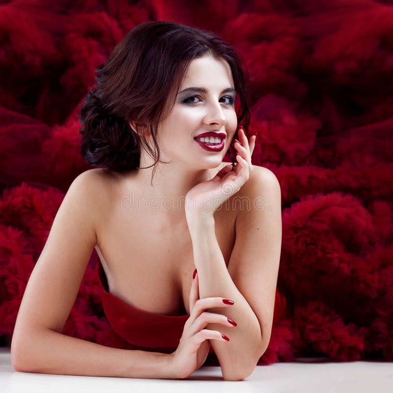 Kvinna för skönhetbrunettmodell i röd klänning för afton Makeup och frisyr för härligt mode lyxig royaltyfri foto