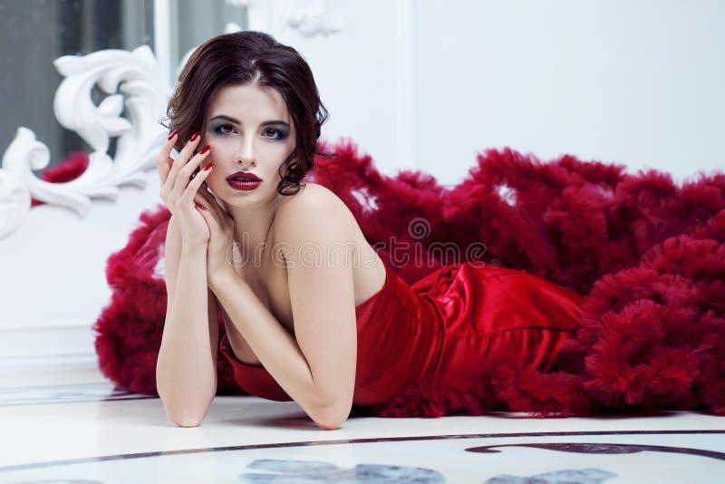 Kvinna för skönhetbrunettmodell i röd klänning för afton Makeup och frisyr för härligt mode lyxig royaltyfri bild