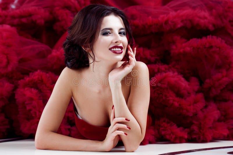 Kvinna för skönhetbrunettmodell i röd klänning för afton Makeup och frisyr för härligt mode lyxig fotografering för bildbyråer