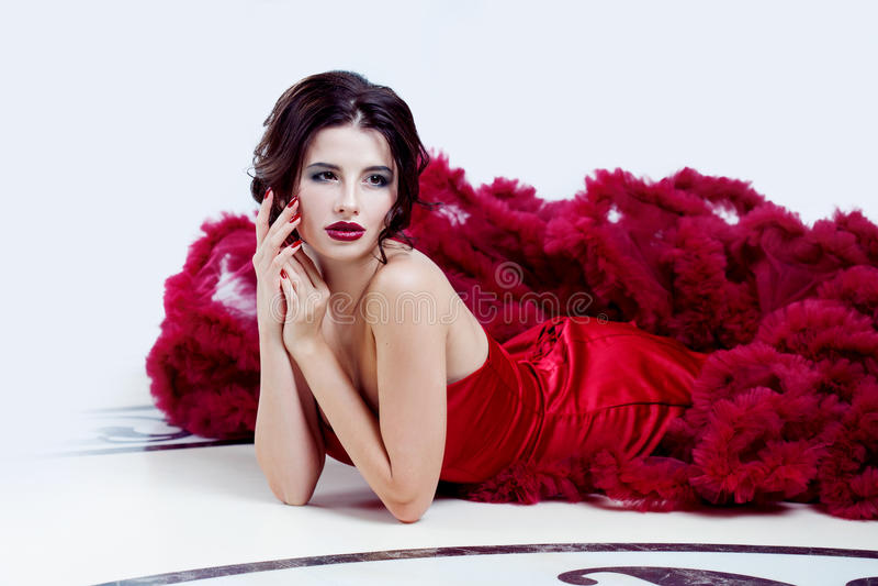 Kvinna för skönhetbrunettmodell i röd klänning för afton Makeup och frisyr för härligt mode lyxig royaltyfria bilder