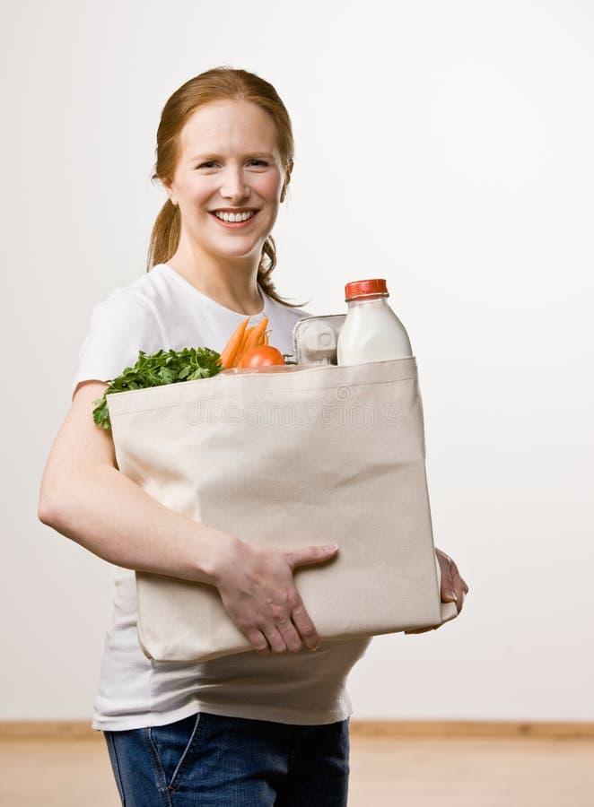 kvinna för specerihandlare för påse bärande lycklig arkivfoto