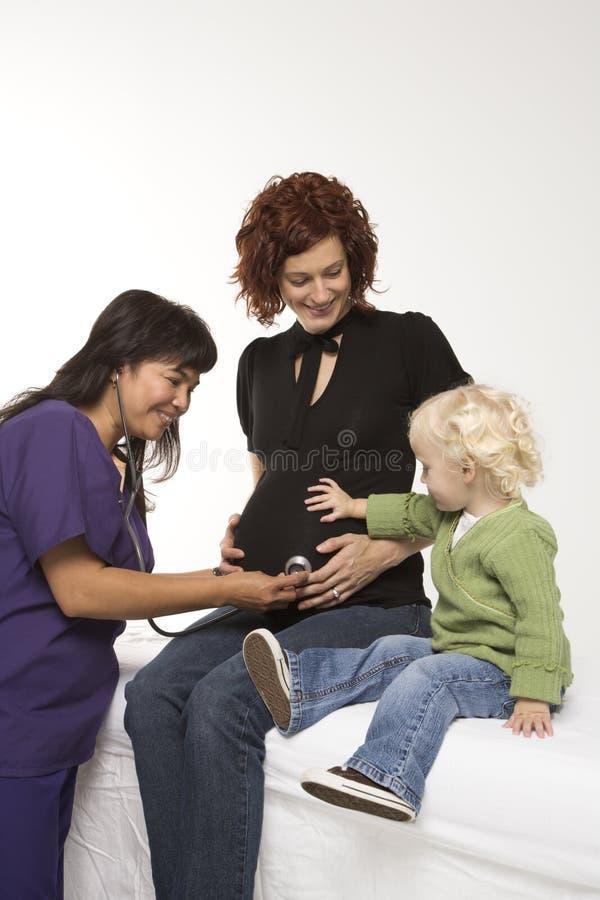kvinna för stetoskop för bukholdingsjuksköterska gravid s royaltyfria foton