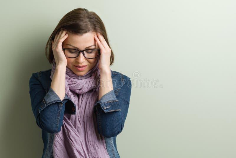 Kvinna för stressad ledsen mitt för stående åldrig Grön vägg för bakgrund, kopieringsutrymme arkivbilder