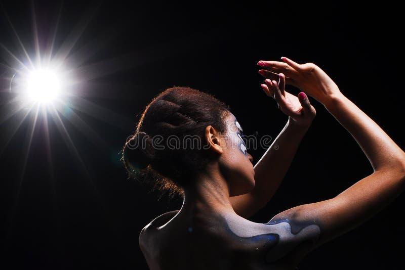 Kvinna för svart afrikan på den svarta bakgrunden med ljus royaltyfria bilder