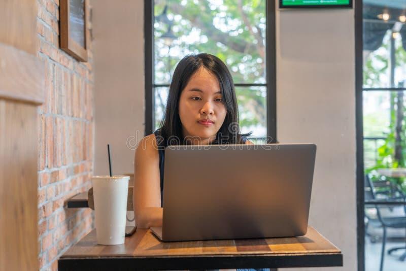 Kvinna för svart hår som arbetar på bärbara datorn på kaffetabellen royaltyfria foton