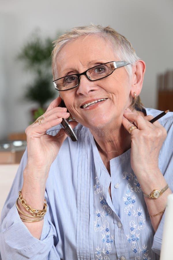 kvinna för telefonståendepensionär arkivbild