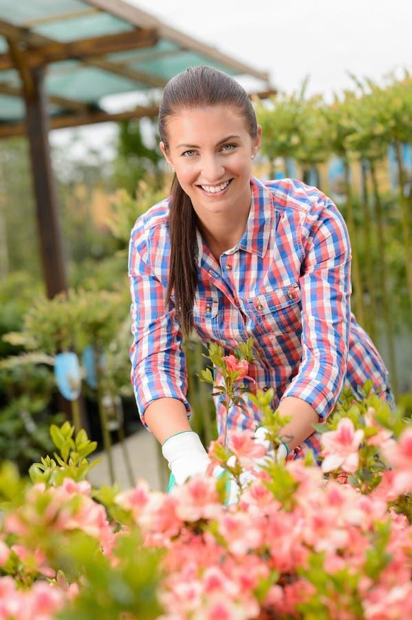 Kvinna för trädgårds- mitt som arbetar, i att le för blomsterrabatt arkivbild