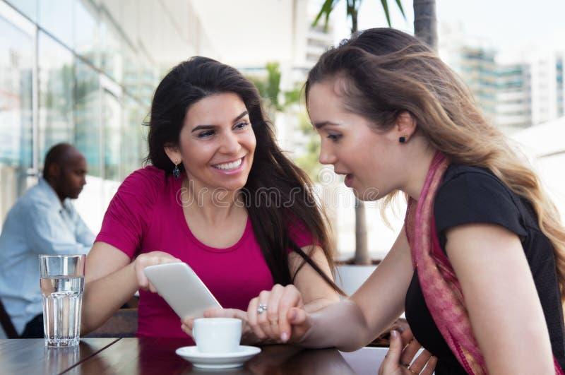 Kvinna för två caucasian som ser telefonen i en restaurang royaltyfri foto
