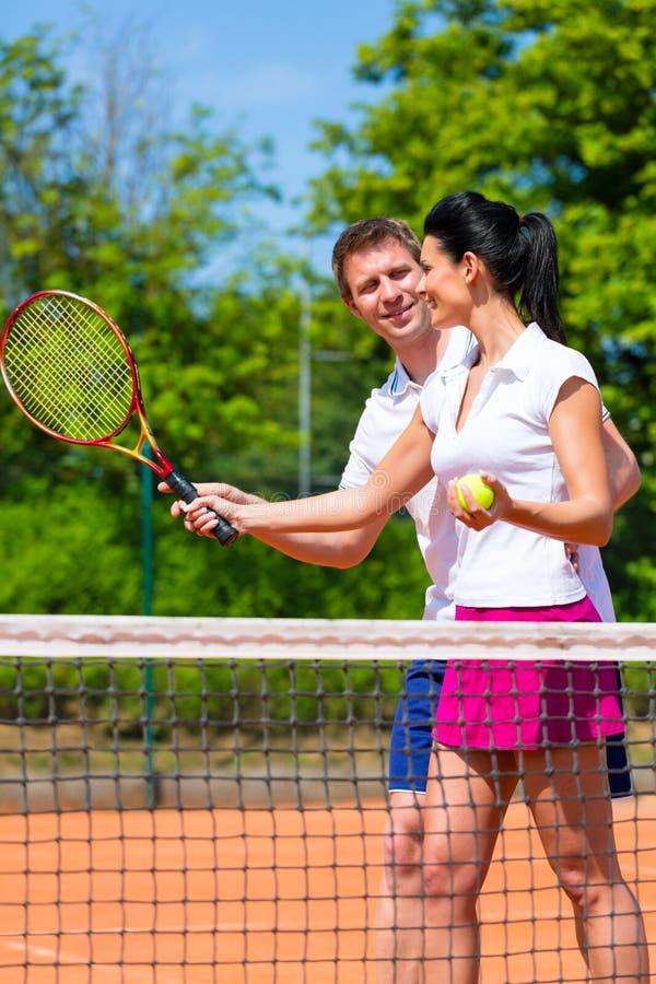 Kvinna för undervisning för tennissportlärare som spelar arkivbild