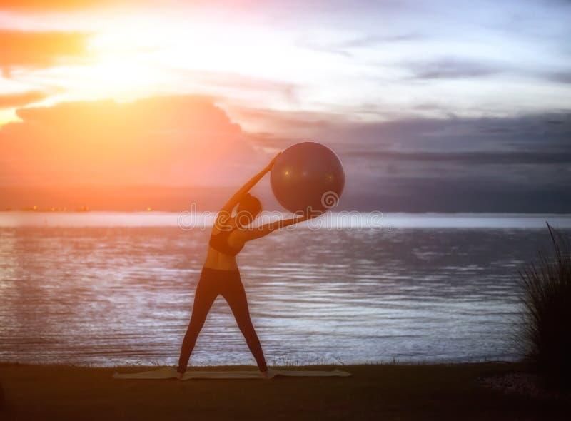 Kvinna för yung för konturyogaboll i stranden royaltyfria bilder