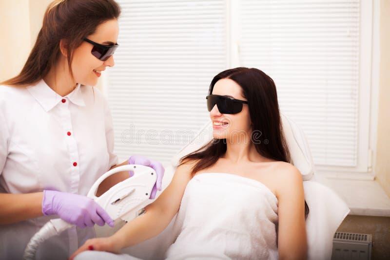 kvinna f?r vatten f?r brunnsort f?r h?lsa f?r huvuddelomsorgsfot Kvinna som får elektrisk hårborttagningsbehandling på hennes han arkivfoto