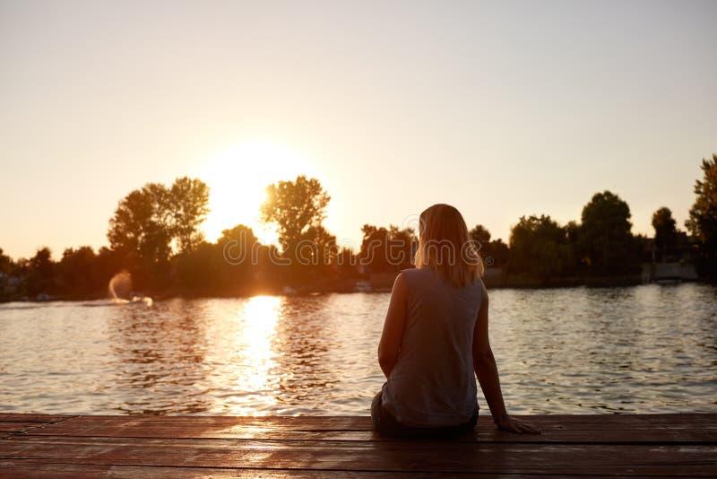 Kvinna från tillbaka sammanträde- och sesolnedgång arkivfoton