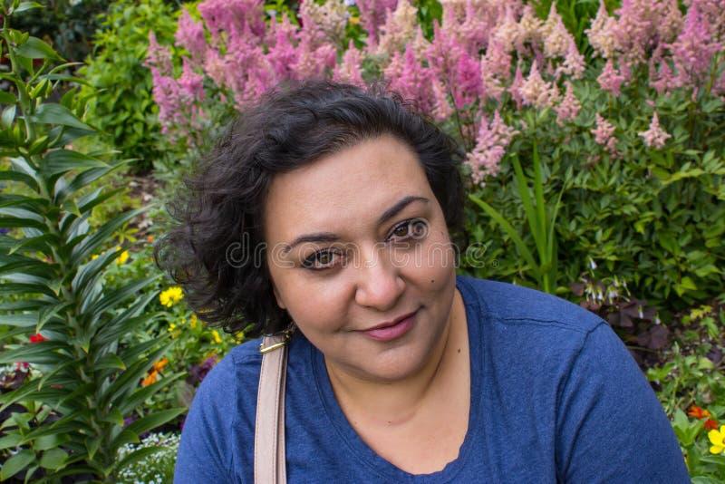 kvinna framme av rosa blommor arkivfoto