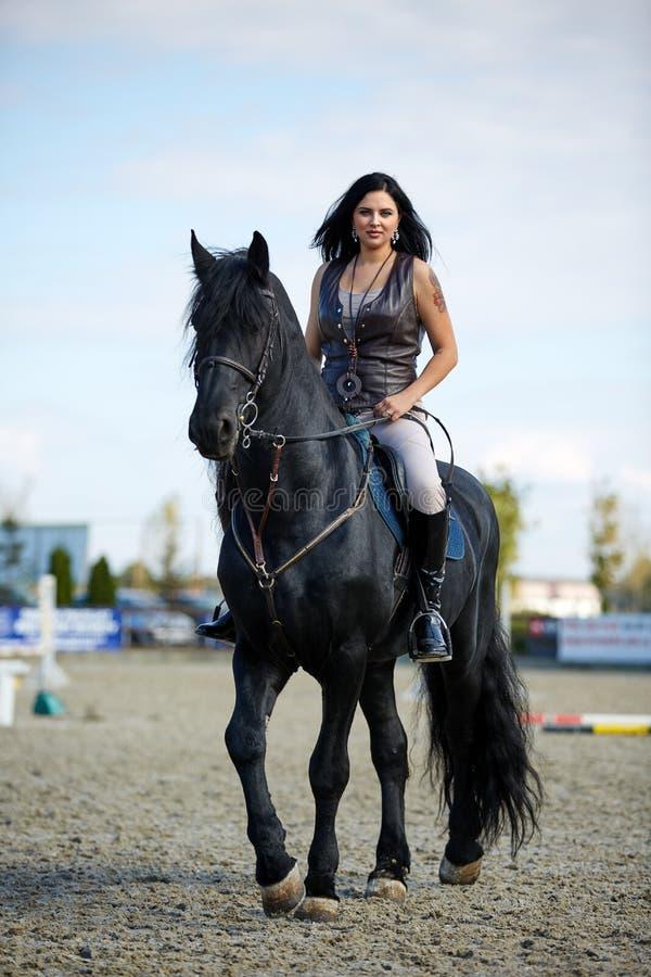 Kvinna grensle en häst royaltyfri bild