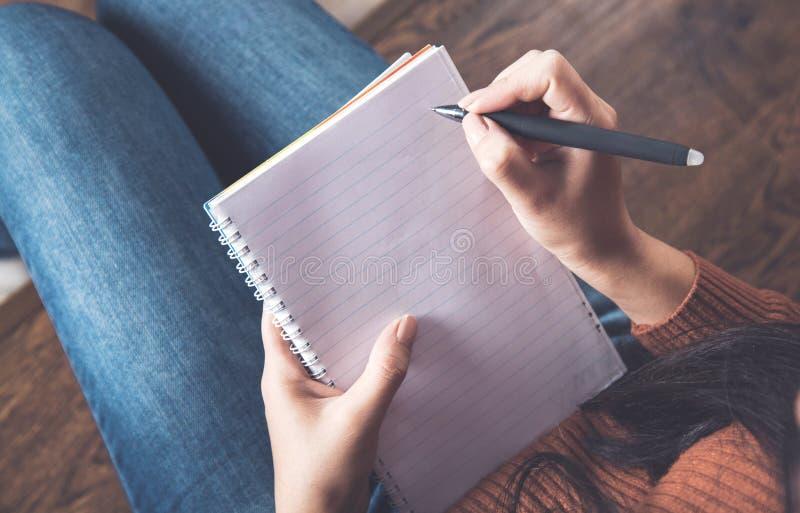 Kvinna handpenna med anteckningsblock arkivfoton