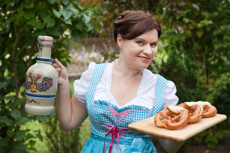 Kvinna i öl och kringla för dirndlklänningholding fotografering för bildbyråer