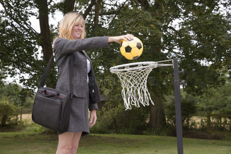Kvinna i affärsdräkt och netto korgboll göra poäng ett mål arkivbilder