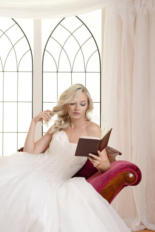 Kvinna i aftonklänning som läser en bok och spelar med hennes hår royaltyfri foto