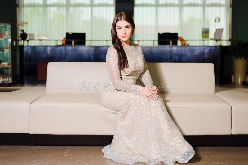 Kvinna i aftonklänningen som poserar på soffan arkivbilder