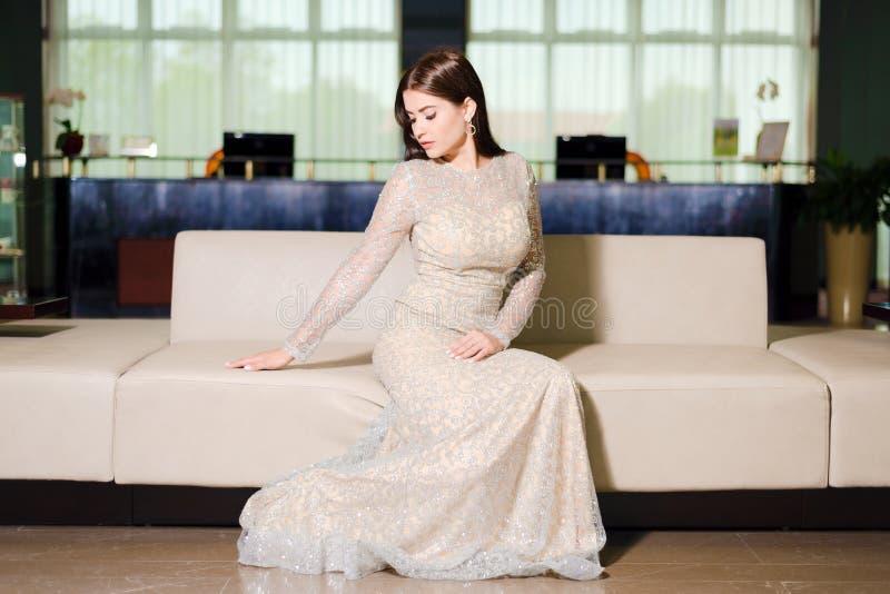 Kvinna i aftonklänningen som poserar på soffan royaltyfria foton