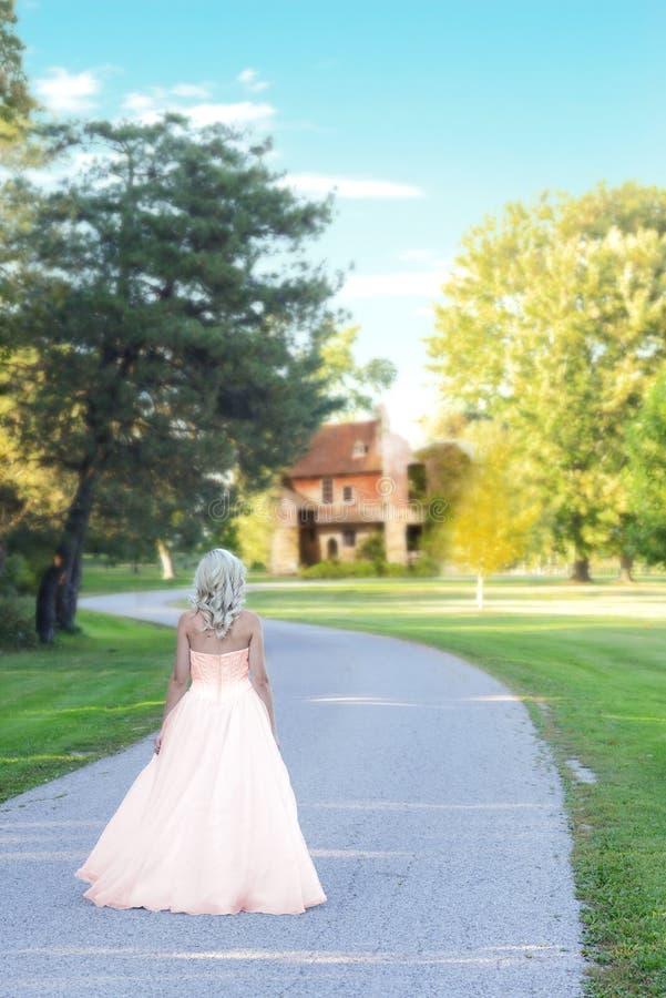 Kvinna i aftontyllklänning som går på vägen till godshemmet royaltyfri fotografi