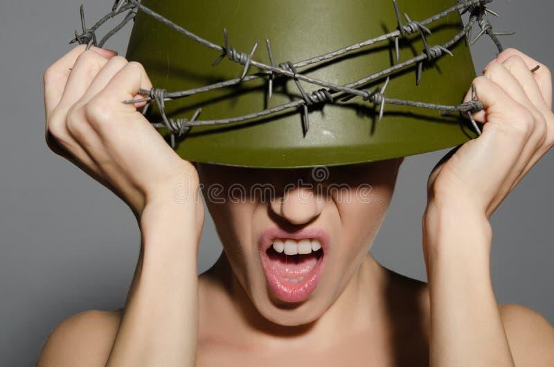 Kvinna i arméhjälm med försett med en hulling - tråd royaltyfri foto