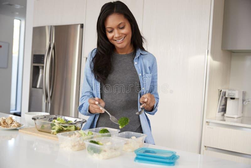 Kvinna, i att förbereda sig för kök som är högt - proteinmål, och att sätta delar in i plast- behållare royaltyfri fotografi
