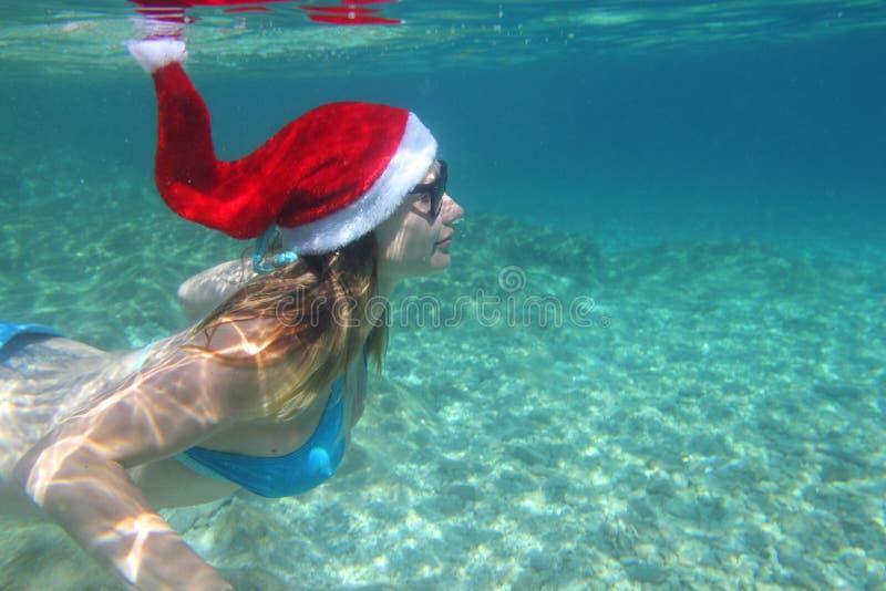 Kvinna, i att simma för jultomtenhatt som är undervattens- royaltyfri bild