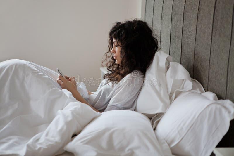 Kvinna, i att smsa för säng royaltyfri foto