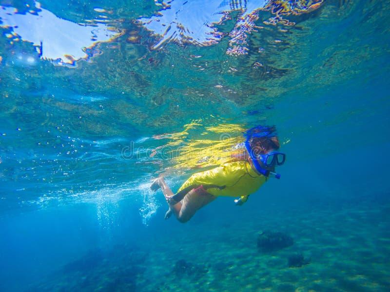Kvinna, i att snorkla det undervattens- fotoet för maskering Kvinnlig snorkel ovanför havsbotten och koraller royaltyfri foto