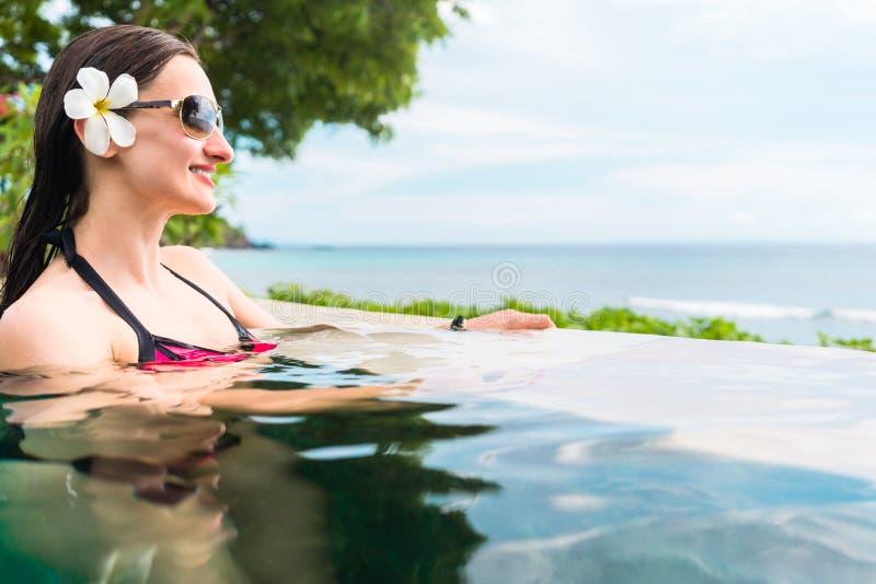 Kvinna i avslappnande simning för semester i pöl fotografering för bildbyråer