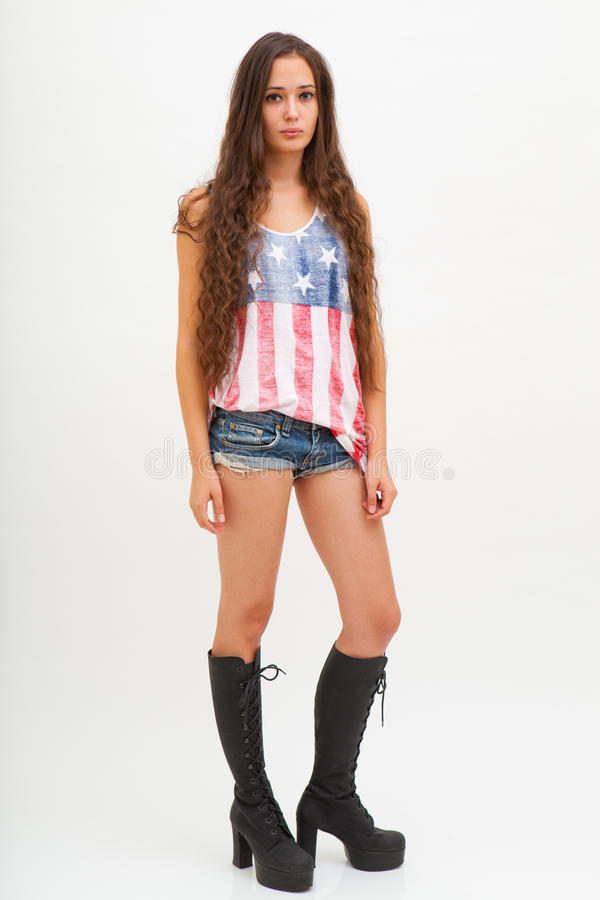 Kvinna i bästa färger av USA flaggan, jeans och svartkängor arkivfoton