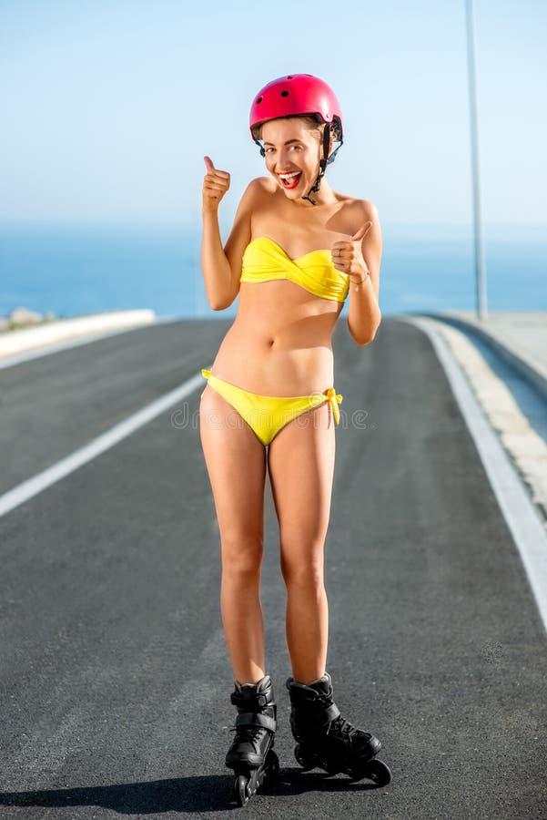 Kvinna i baddräkt med rullar på huvudvägen arkivfoton