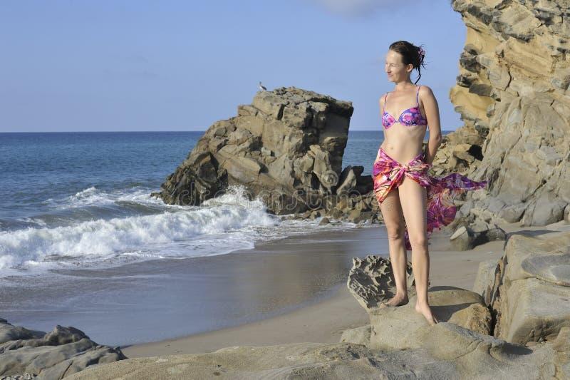 Kvinna i baddräkt och pareo på stranden arkivfoto
