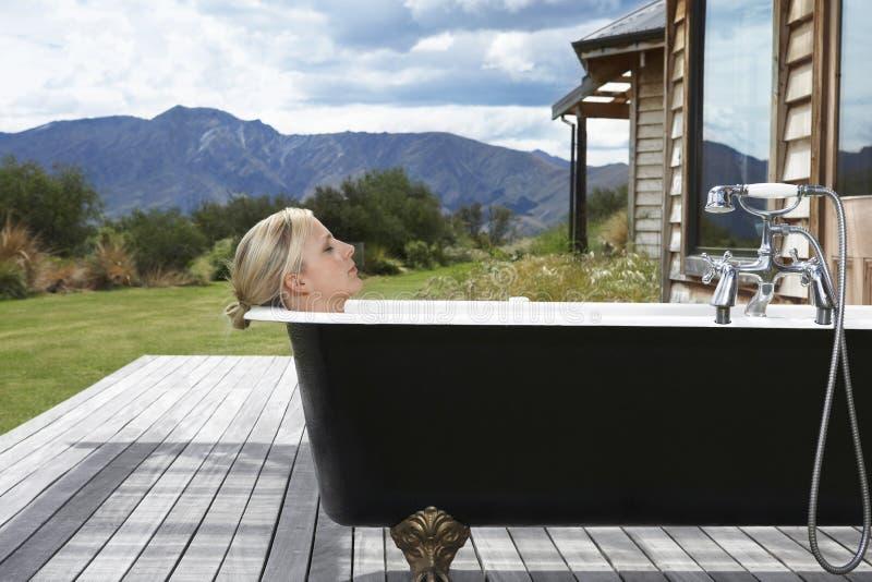 Kvinna i badkar på farstubron mot berg royaltyfria bilder