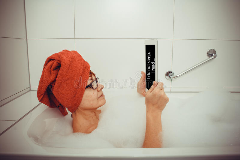 Kvinna i badkaret med minnestavladatorer, retro stil royaltyfri fotografi