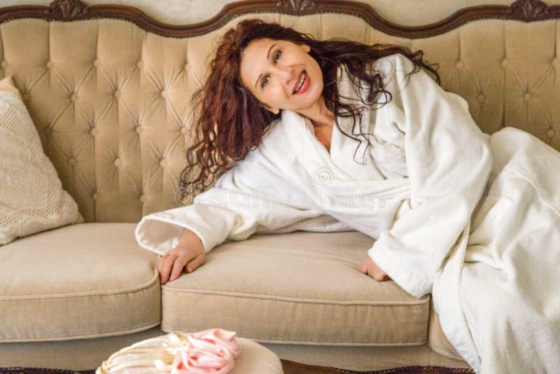 Kvinna i badrock som vilar på soffan royaltyfria bilder