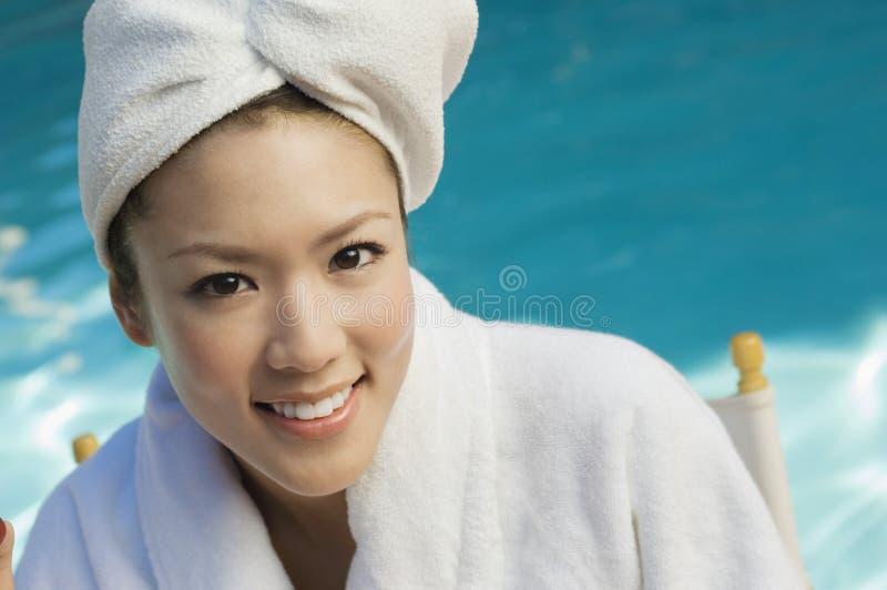 Kvinna i badrock vid pölen royaltyfria bilder