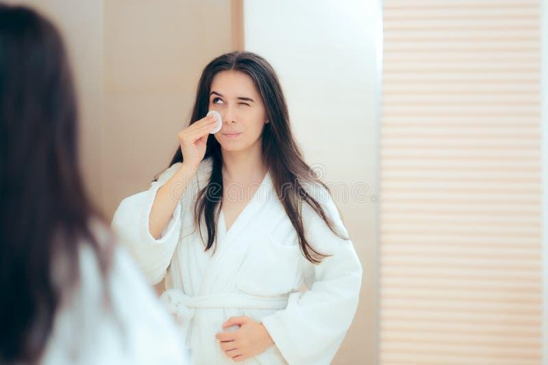 Kvinna i badrocken som gör ren hennes framsida med sminkborttagningsmedel arkivbild