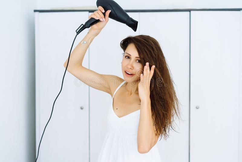 Kvinna i badrocken som torkar hennes hår med torken över vit bakgrund fotografering för bildbyråer