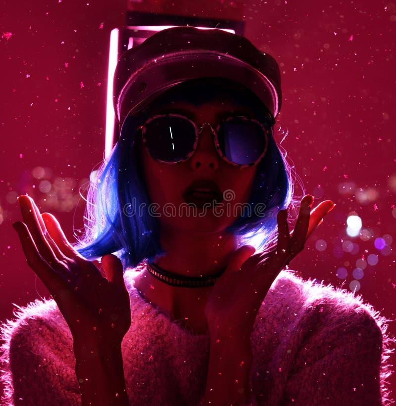 Kvinna i begreppet för vinter för gatastilmode som bär guld- hattlock- och rundasolglasögon i rosa neonljus under snöflingor royaltyfri fotografi