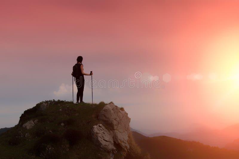 Kvinna i bergen bara i en brännhet himmel arkivfoton
