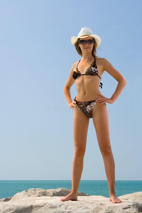 Kvinna i bikini och hatt på sommarhavsstranden, sexigt flickaanseende royaltyfri fotografi