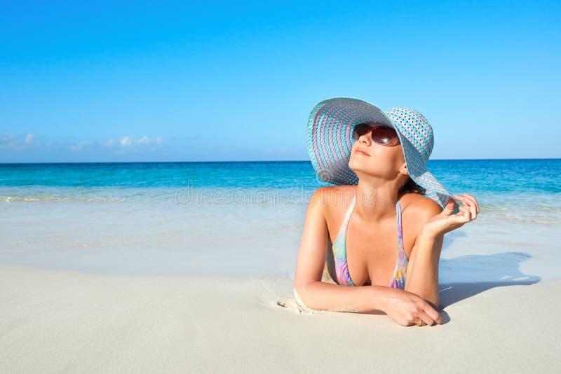 Kvinna i bikini och sommarhatt som tycker om på den tropiska stranden arkivfoto