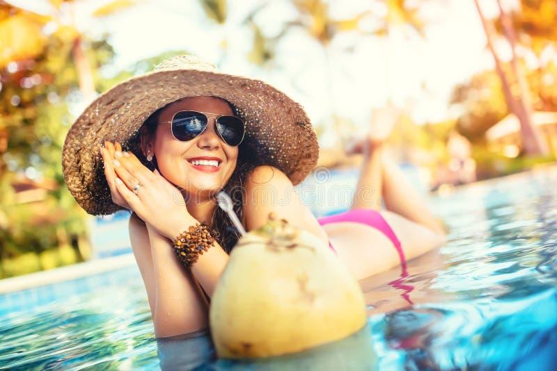 Kvinna i bikini på poolside som dricker fruktsaft från den långa coctailen för kokosnöt Bekymmerslöst och avslappnande feriebegre arkivbild